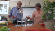 MS PAN Shot of Senior mixed race couple prepping salad in kitchen / Cape Town, Western Cape, South Africa
