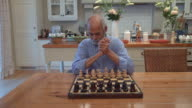 MS Shot of senior mixed race man playing chess in kitchen / Cape Town, Western Cape, South Africa