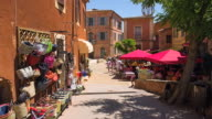 MS Shot of shops with people sitting in restaurant in Ocre Village / Roussillon, Provence, France