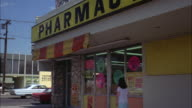 MS Shot of sign 'pharmacy' over window of building