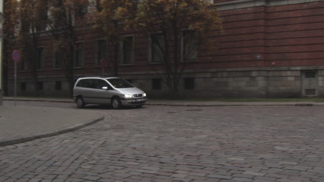 MS TS Shot of Silver Van moving on street / Riga, Latvia