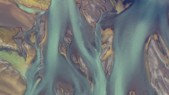 MS AERIAL DS ZO Shot of Silvery/turquoise river patterns / Iceland
