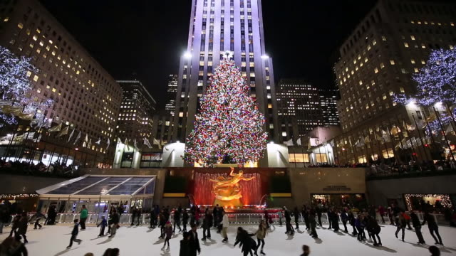 MS Shot of Skaters and illuminated Christmas Tree at Rockefeller Center at night / New York, United States