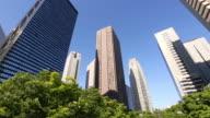 MS PAN Shot of skyscrapers behind waving fresh green trees at district of West Shinjuku / Shinjuku ku, Tokyo, Japan