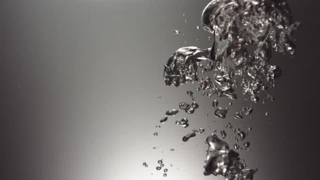 CU SLO MO Shot of Small cluster of bubbles in dark tank / United Kingdom