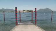 WS Shot of small jetty in front of Borromean Island of lake Maggiore with Isola Superior / Stresa, Piedmont, Italy