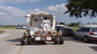 WS POV Shot of Small Pressurized Rover drives down street in NASA Johnson Space Center campus / Houston, Texas, United States