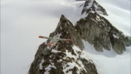 MS AERIAL Shot of small single engine airplane flying over snow covered rugged mountain range and low hanging clouds
