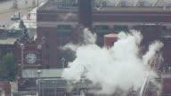 MS AERIAL Shot of Smoke billowing around clocktower at Anheuser Busch brewery / St Louis, Missouri, United States
