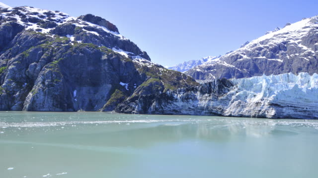 Shot of snow covered mountains and small ice glaciers floating in the water, Alaska
