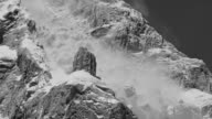 MS TD Shot of snow covering mountain as an avalanche begins, snow and boulders tumble down mountain