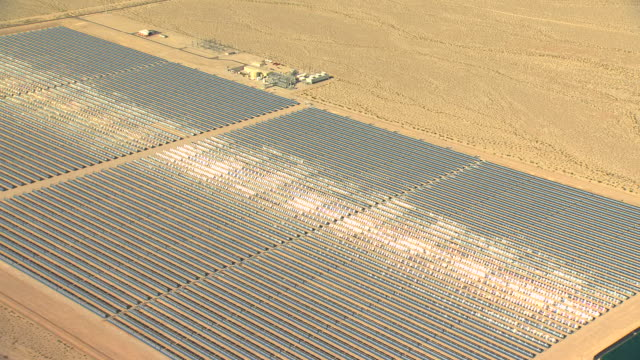 MS AERIAL ZI Shot of solar panels with bright sunshine moving on panels at Nevada Solar One solar power plant surrounded by desert / Boulder City, Nevada, United States