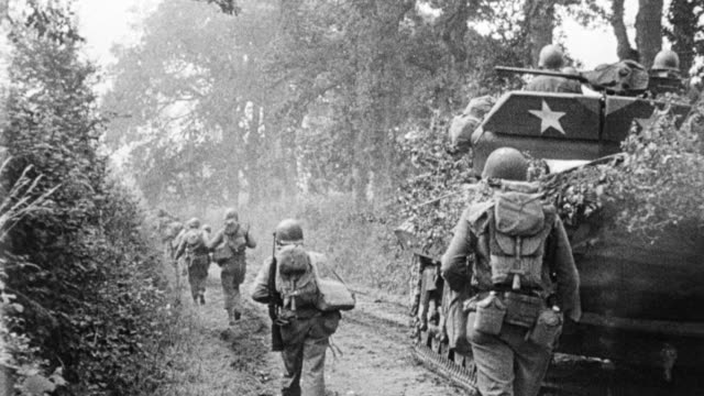 MS Shot of soldiers walking with tank and jeep, military news reel footage
