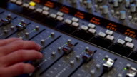 MS TD Shot of sound mixing desk controls to CU of hand moving sliders up and down / United States