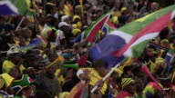 MS SLO MO Shot of South African fans blowing vuvuzela's and flying flags / Johannesburg, Gauteng, South Africa