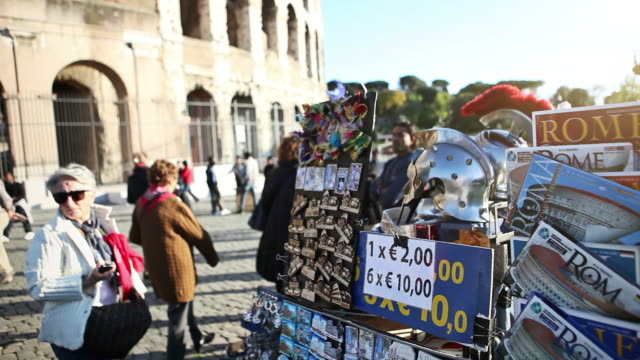 MS Shot of souvenirs street vendor under Coliseum with tourists and people passing by / Rome, Italy