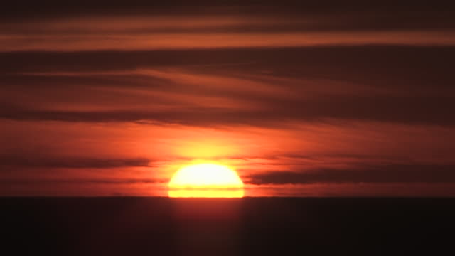 MS T/L Shot of Spectacular Sunset with Deep Red Fire Ball Sun setting into oceans in Brilliant Sky / Malibu, California, United States