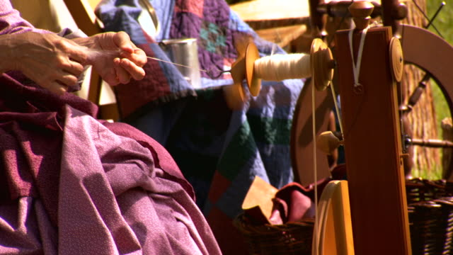 MS PAN Shot of spinning wheel to woman hand as she spins wool into yarn / Fairfax, Virginia, United States