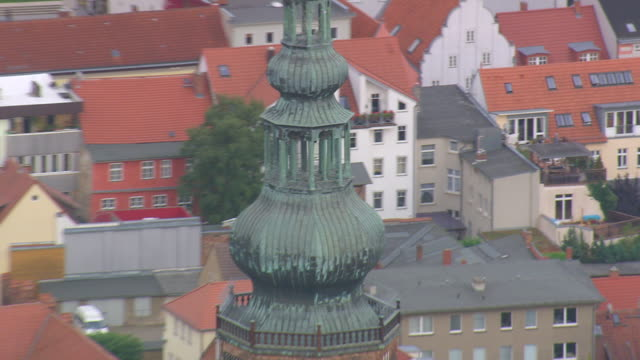 MS AERIAL Shot of St. Nikolai cathedral tower with trees and houses surrounded / Germany