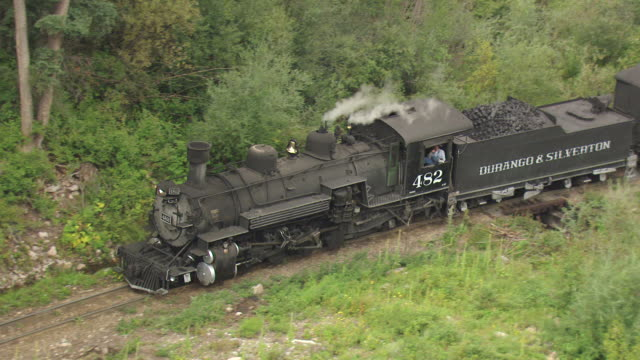 MS TS AERIAL Shot of steam train emerges from trees and steam coming out of stack and conductor at window / Telluride, Colorado, United States