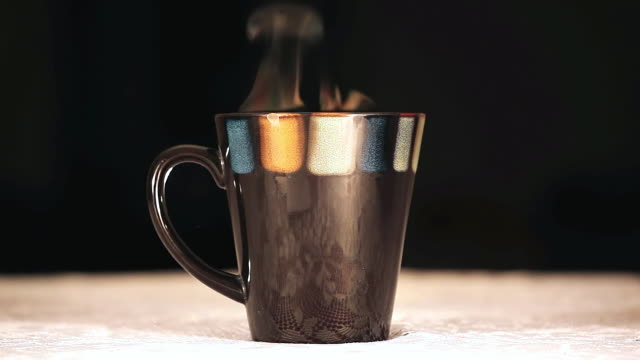 MS Shot of Steaming hot cup of coffee against black back side / Endicott, New York, United States