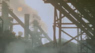 MS PAN Shot of Steel structures outside of factory with smoke billowing at sunset