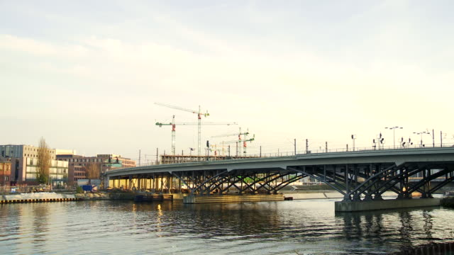 MS T/L Shot of Subway train in Berlin moving across bridge over river with construction site in back side / Berlin, Germany