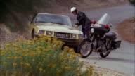 MS Shot of switzerland motorcycle policeman stopping gold citroen sedan on a mountain highway