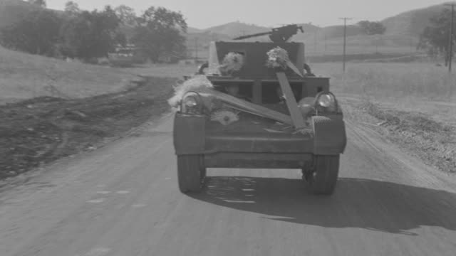 MS POV Shot of tank moving toward on dirt street