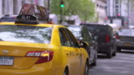 Shot of taxis and other traffic driving down 5th Avenue in Manhattan on a Sunny Day