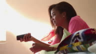 MS Shot of teenage girl watching television in her bedroom / Lamy, New Mexico, United States