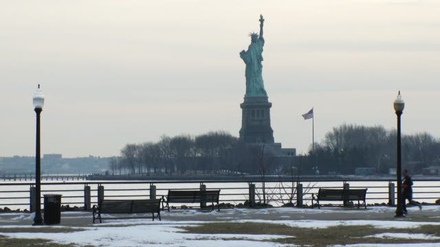 Shot of the back of the Statue of Liberty taken from Liberty State Park in Jersey City. A man jogs by the shot