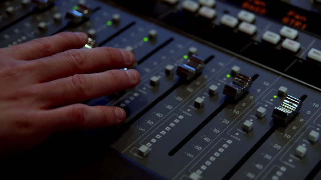 CU Shot of The hand moves sound mixing desk sliders up and down / United States