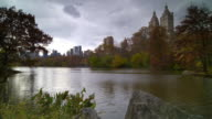 Shot of The Lake in Central Park, New York City. The trees are in full fall colors and the San Remo Apartments and other buildings can be seen in the skyline. A family of ducks goes across the water