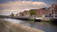 Shot of the River Liffey in Dublin, Ireland on a sunny day. People and traffic travel on the streets along the banks