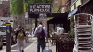 Shot of the sign on the exterior of The Actors Playhouse in downtown Manhattan. People walk on the sidewalk underneath the sign