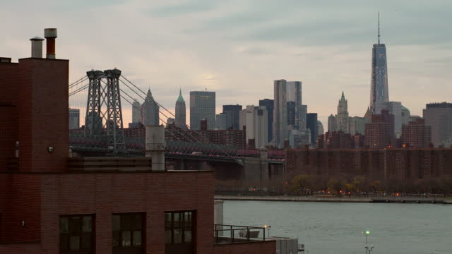 Shot of the Williamsburg Bridge against the Manhattan Skyline.  One World Trade Center is clearly seen
