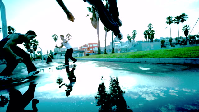 WS SLO MO LA Shot of Three guys doing side flip one after other with reflection from ground / Venice, California, United States