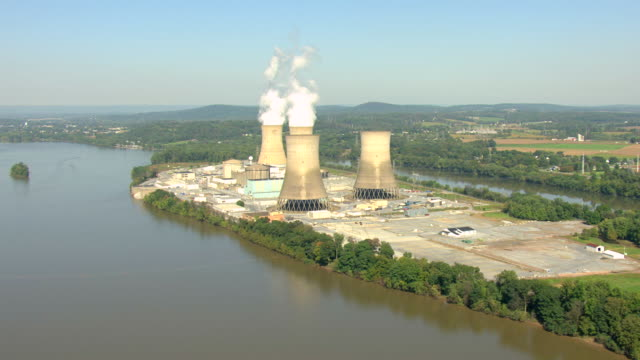 MS AERIAL Shot of three Mile Island Nuclear Generating Station by Susquehanna River in Dauphin County / Pennsylvania, United States