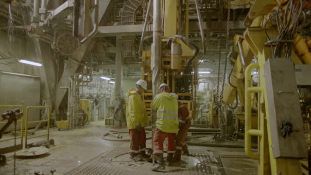 WS SLO MO Shot of Three Roughnecks fastening drill through hole in floor Rain Oil rig in / The North Sea