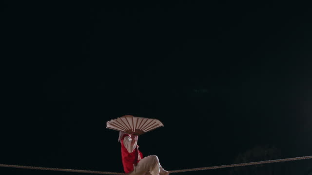 MS Shot of tightrope walker doing acrobatics on high wire at night / Gyeonggido, South Korea