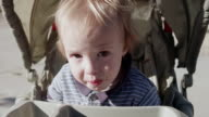 CU Shot of toddler baby eating his healthy sandwich snack and smiling in his stroller seat on warm summer day / Beaverton, Oregon, United States