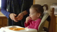 MS Shot of Toddler eats food placing on high chair tray by her mother / Chelsea, Michigan, United States