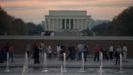 MS Shot of tourists admiring gold stars representing military deaths at World War II Memorial with Lincoln Memorial during sunset on National Mall / Washington, District of Columbia, United States