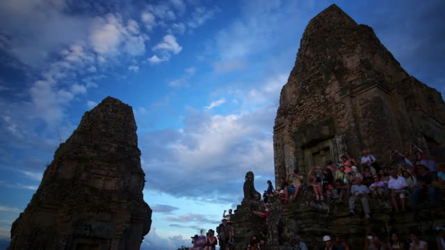 MS T/L LA Shot of Tourists at dusk sitting on Pre Rup temple, busy human activity as sky darkens / Angkor Wat, Cambodia