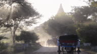 MS Shot of Tourists driving with horse carriage and monks walking on road at sunset / Bagan, Mandalay Division, Myanmar
