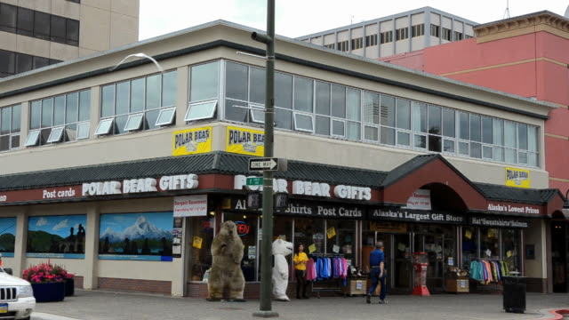 MS Shot of tourists on 4th Avenue and F Street with Polar Bear gift shop with red trolley / Anchorage, Alaska, United States