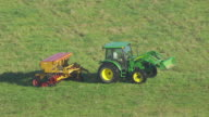 MS AERIAL TS ZO Shot of tractor in field to reveal countryside / Missouri, United States