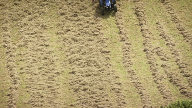 MS AERIAL Shot of tractor working in field / Midi Pyrenees, France