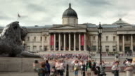 MS PAN T/L Shot of Trafalgar Square Central London, Sir Edwin Landseers lion sculptures and national gallery in back side visitors moving and cloudy sun comes out / London, Greater London, United Kingdom